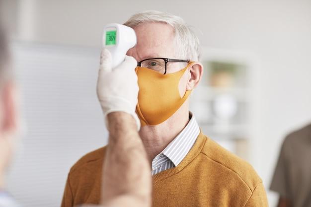 Aufnahme eines nicht erkennbaren arztes, der die temperatur eines älteren mannes mit maske in einer klinik oder einem krankenhaus überprüft, platz kopieren