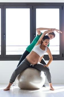 Aufnahme eines physiotherapeuten, der einer schönen schwangeren frau hilft, pilates-übungen mit ball zu machen, der sich auf die geburt vorbereitet.