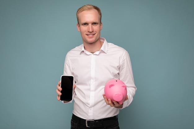 Aufnahme eines positiv lächelnden jungen, gutaussehenden blonden mannes mit aufrichtigen emotionen, der ein lässiges weißes hemd trägt, isoliert auf blauem hintergrund mit kopierraum, hält rosa sparschwein für geld und zeigt smartphone mit