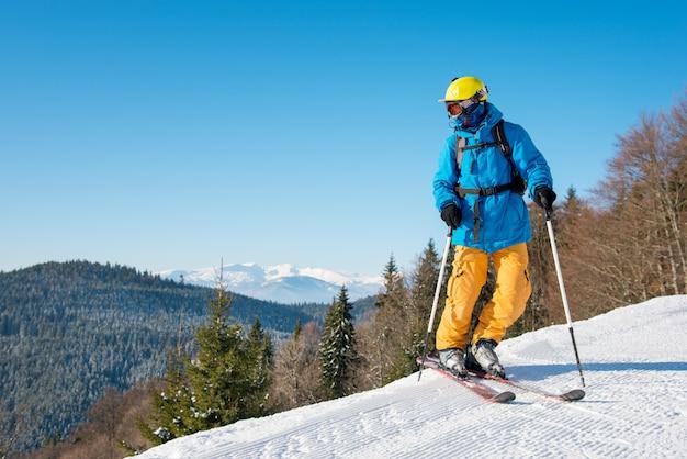 Aufnahme eines professionellen skifahrers, der auf frischem pulverschnee in den bergen des winterresorts ski fährt