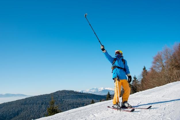 Aufnahme eines professionellen skifahrers in voller länge, der ein selfie mit einem selfie-stock macht, der auf der piste posiert. blauer himmel, berge und winterwald auf dem hintergrund