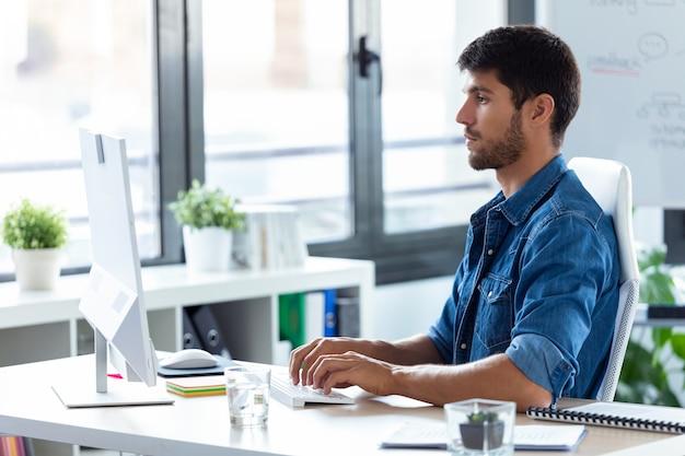 Aufnahme eines softwareentwicklers, der im modernen startup-büro mit dem computer arbeitet.