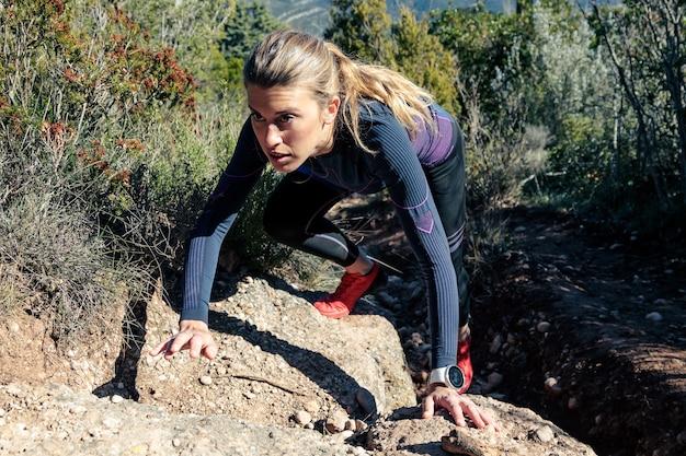 Aufnahme eines sportlichen wanderers der jungen frau, der steiles felsiges gelände auf dem berg klettert.