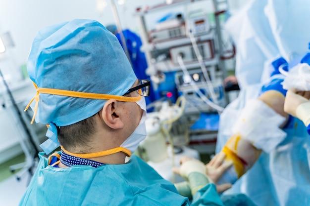 Aufnahme eines technologisch fortschrittlichen operationssaals mit menschen. chirurgie-prozess. operationssaal mit arbeitsgeräten, beleuchtung und computern mit chirurgen.