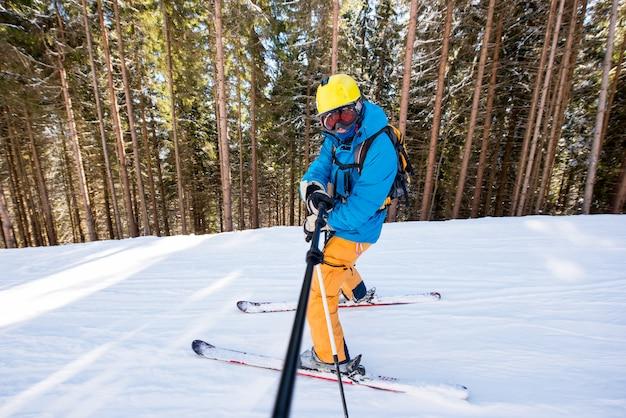 Aufnahme in voller länge von einem professionellen skifahrer, der ein selfie-bild mit einem einbeinstativ beim skifahren macht