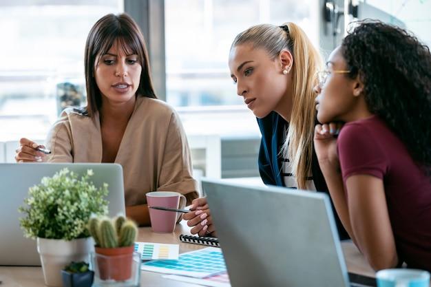 Aufnahme von drei modernen geschäftsfrauen, die in einem gemeinsamen arbeitsbereich sprechen und die neuesten arbeiten am computer überprüfen