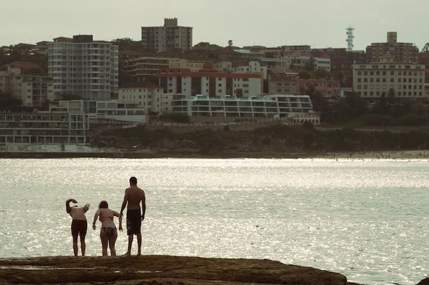 Aufnahme von freunden auf augenhöhe, die in bondi beach, sydney, australien, ins meer springen