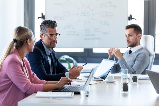 Aufnahme von geschäftsleuten, die während eines meetings im büro zusammen im konferenzraum diskutieren.