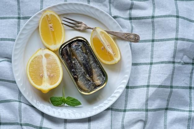 Aufnahme von oben auf eine dose sardinen in öl, mit einigen basilikumblättern und zitronenspalten auf einer küchentischdecke