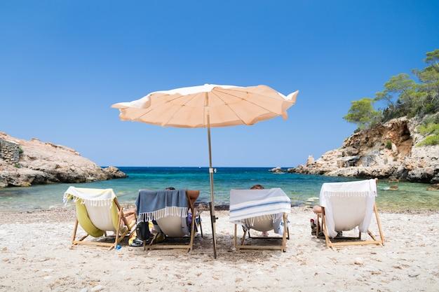 Aufnahme von vier personen in sonnenliegen am strand