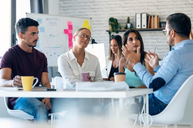 Aufnahme von zufälligen multiage-geschäftsleuten, die im büro arbeiten und über ihr neues projekt sprechen.