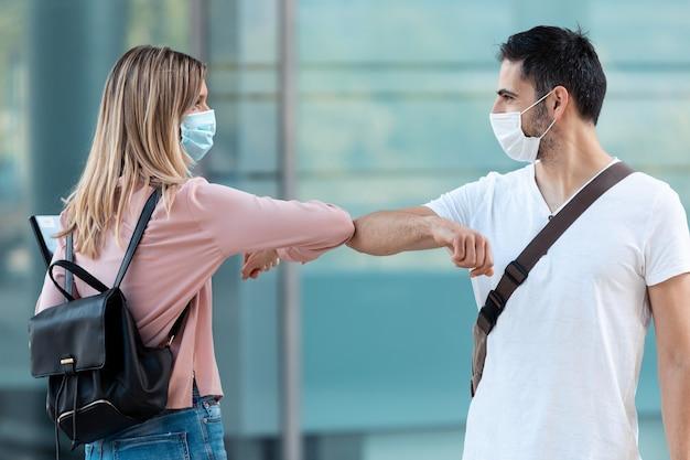 Aufnahme von zwei freunden, die während des ausbruchs von covid-19 auf dem universitätscampus eine chirurgische maske tragen und mit dem ellbogen winken. soziale distanzierung und neues normales konzept.