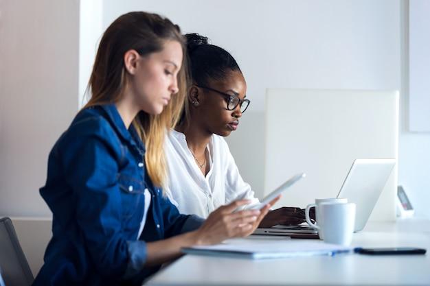 Aufnahme von zwei hübschen jungen geschäftsfrauen, die mit digitalem tablet und laptop im büro arbeiten.