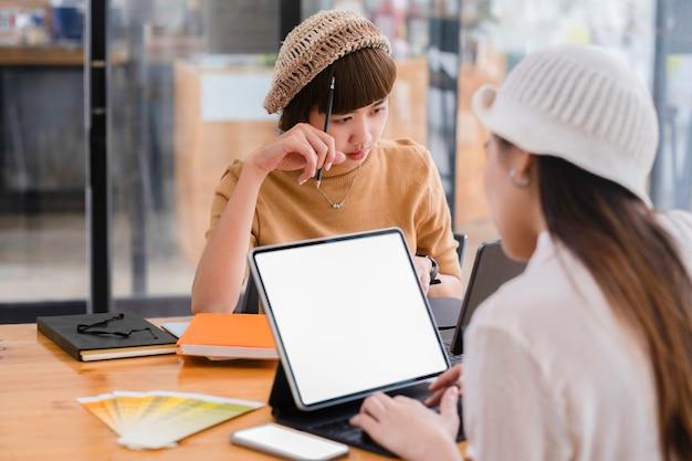 Aufnahme von zwei jungen frauen, die gemeinsam an einem digitalen tablet arbeiten. kreative weibliche führungskräfte treffen sich in einem büro mit tablet-pc und lächelnd.