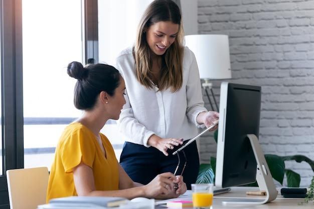 Aufnahme von zwei jungen geschäftsfrauen, die sich unterhalten und ihre letzte arbeit im digitalen tablet im büro überprüfen.