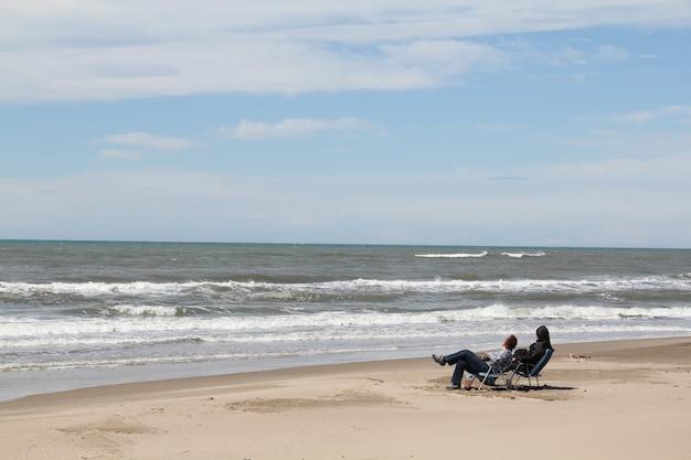 Aufnahme von zwei personen, die auf den stühlen am strand sitzen und auf die meereswellen schauen und sich entspannen?