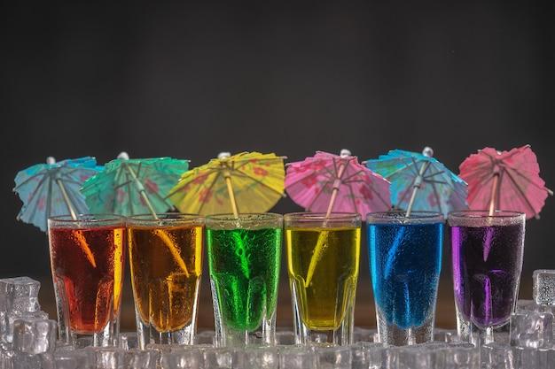 Aufnahmen mit mehrfarbigem alkohol, in einer reihe stehend und mit cocktailschirmen dekoriert