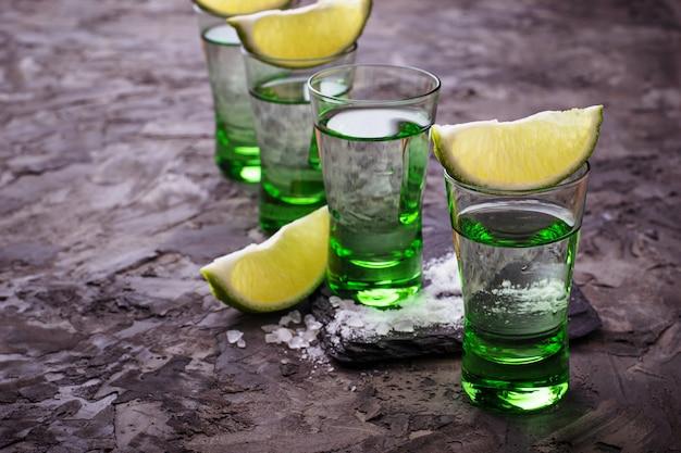 Aufnahmen von mexikanischem silber-tequila mit kalk und salz. selektiver fokus