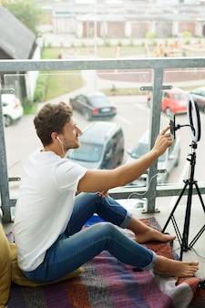 Aufnehmen von videos oder streaming. junge hübsche bloggerin, die zu hause arbeitet.