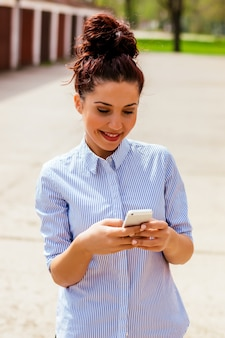 Aufpassende videos der frau in einem intelligenten telefon draußen