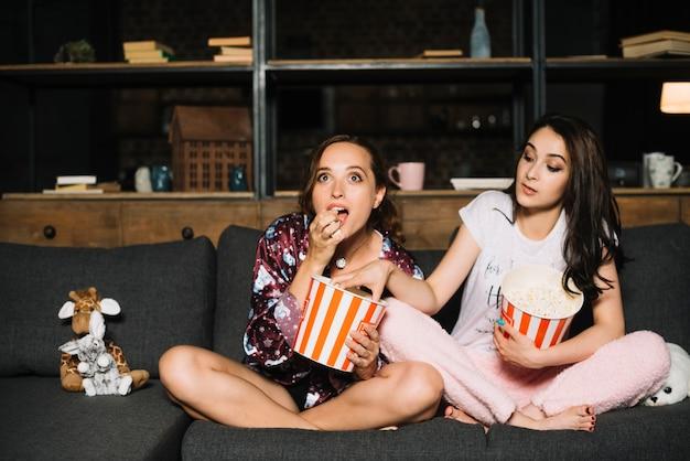 Aufpassender film der frau während ihr freund, der popcorn von ihrem eimer nimmt
