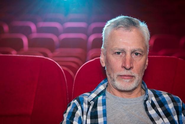 Aufpassender film des älteren mannes im kino