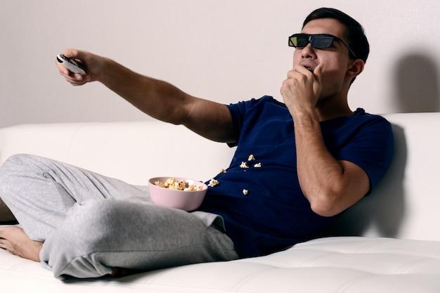 Aufpassender film des jungen mannes in den gläsern 3d und essen des popcorns