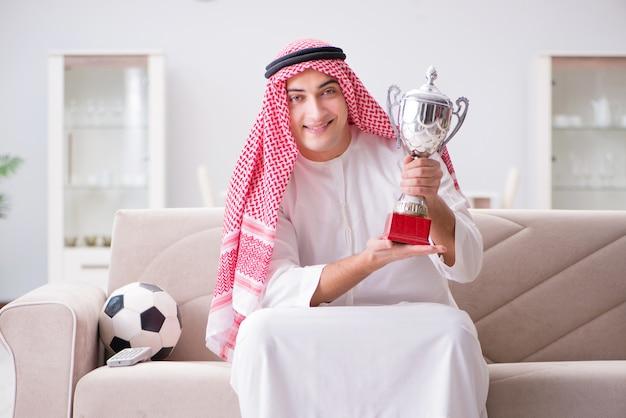 Aufpassender fußball des jungen arabischen mannes, der auf sofa sitzt