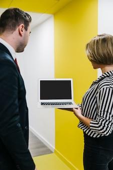 Aufpassender laptop des mannes und der frau im büro