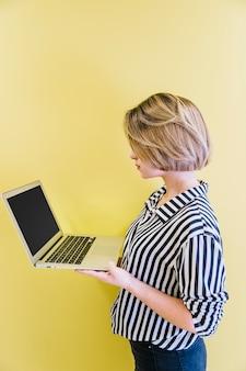 Aufpassender laptop des modischen mädchens auf gelb