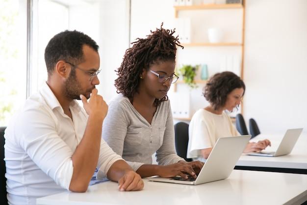 Aufpassender praktikant des mentors, der an computer arbeitet