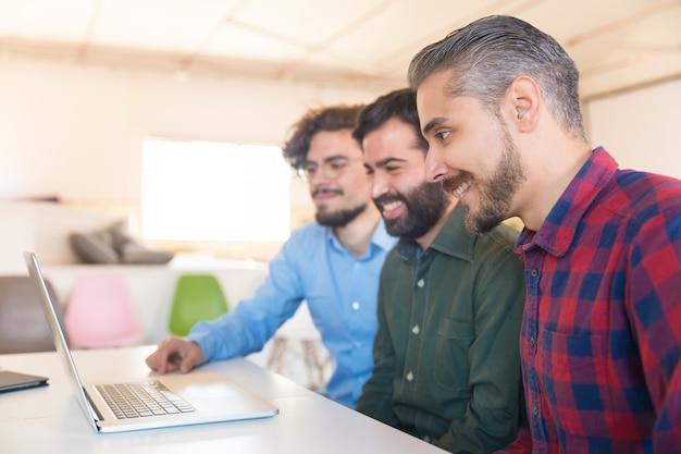 Aufpassender videoinhalt des glücklichen kreativen teams auf monitor