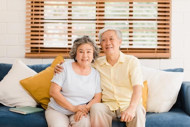 Aufpassendes fernsehen der asiatischen älteren paare im wohnzimmer zu hause, süße paare genießen liebesmoment beim auf dem sofa liegen, wenn sie zu hause entspannt werden.