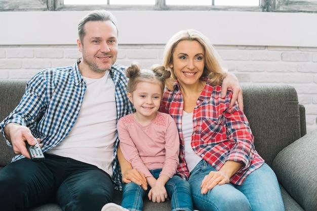 Aufpassendes fernsehen der glücklichen familie zusammen auf sofa