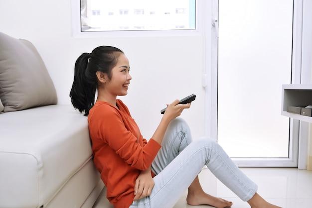Aufpassendes fernsehen der jungen asiatischen frau beim sitzen