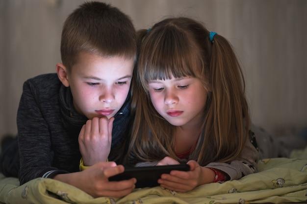 Aufpassendes video von zwei kinder bruder und schwester auf smartphoneschirm zusammen.