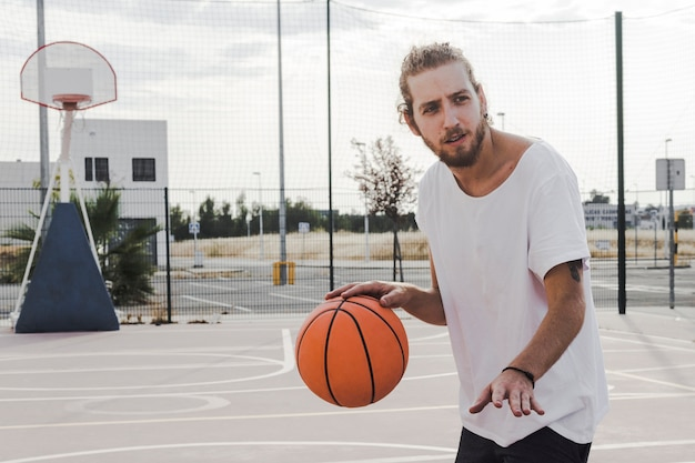 Aufprallender basketball des jungen mannes im gericht