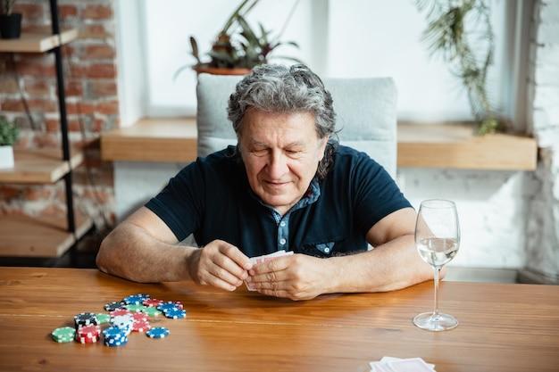 Aufregend. glücklicher reifer mann, der karten spielt und wein mit freunden trinkt.