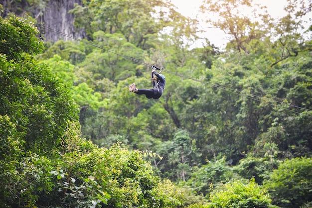 Aufregende sportabenteueraktivität der zipline, die am großen baum im wald bei vang vieng laos hängt