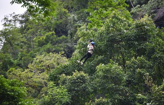 Aufregende sportabenteueraktivität der zipline, die am großen baum im wald bei vangvieng laos hängt