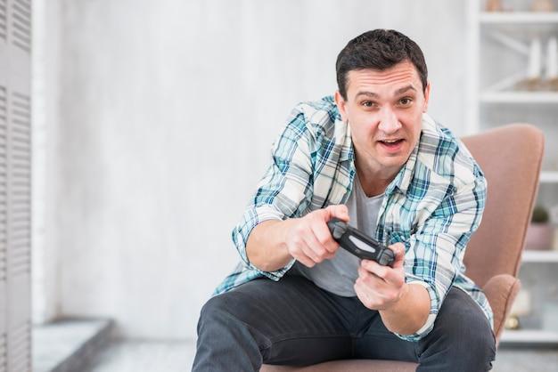 Aufregender mann, der im lehnsessel sitzt und mit gamepad spielt