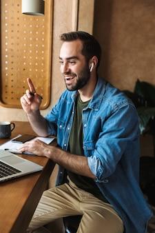 Aufregender optimistischer mann, der ein jeanshemd trägt und ohrstöpsel mit laptop und zwischenablage verwendet, während er im café drinnen arbeitet