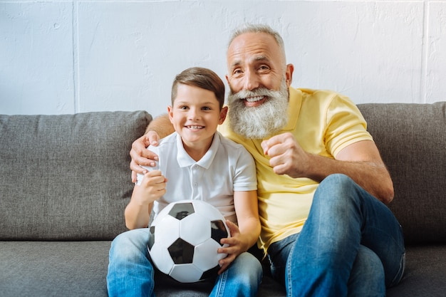 Aufregendes spiel. optimistischer älterer mann, der auf der couch neben seinem enkel mit einem ball im schoß sitzt und ein wichtiges fußballspiel beobachtet und aufgeregt aussieht