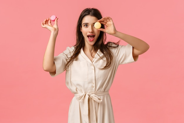 Aufregung, feiertage und süßspeisekonzept. elegante attraktive junge frau genießen, das köstliche lebensmittel zu essen und macarons ein auf auge halten, der offene keuchende unterhaltene mund und stehen rosa