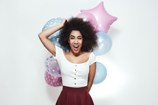Aufregung und glück überraschten die junge afroamerikanische frau, die bunte luftballons anhält