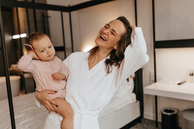 Aufrichtige frau im weißen bademantel lacht und hält baby in ihren armen. kind legt telefon an ihr ohr.