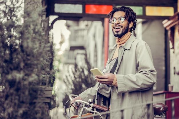 Aufrichtige gefühle. hübscher mann, der ein lächeln auf seinem gesicht hält, während er sich über gute nachrichten freut