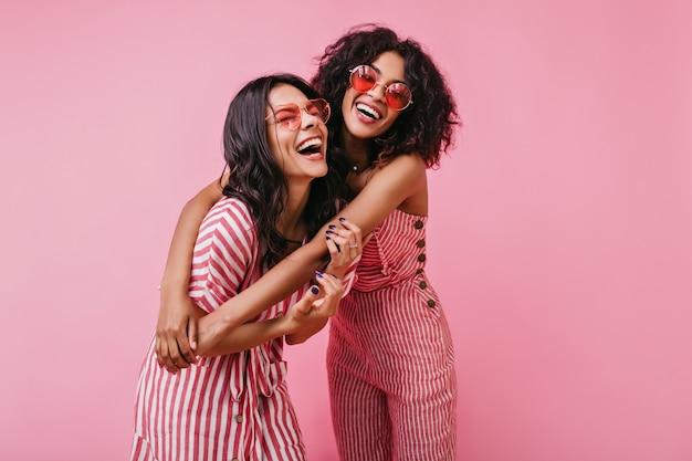 Aufrichtige mädchen mit strahlendem lächeln posieren in gestreiften rosa overalls. sommeraufnahme von lustigen modellen.