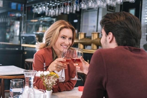 Aufrichtiges positives paar, das wein trinkt und plaudert