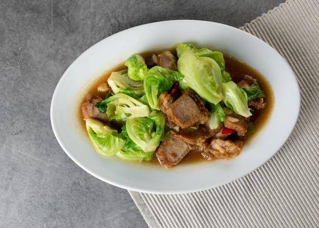 Aufruhr fried baby cabbage mit knusperigem schweinefleisch auf platte, asiatisches lebensmittel